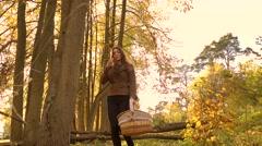Brunette girl walking in autumn forest holding a basket. 4K steadicam clip Stock Footage