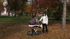 Mother walking with a baby pram (stroller, carriage) in the park. Autumn nature Stock Footage