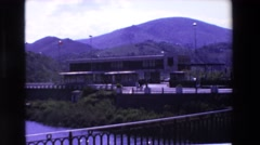 1969: a building and mountains as seen across the water on a bridge LOURDES Stock Footage