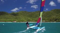 Young man sailing a catamaran at Cinnamon Bay Beach, St John Stock Footage