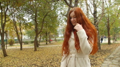 Girl in a white overcoat, with long red hair, sweeping the avenue autumn park. Stock Footage