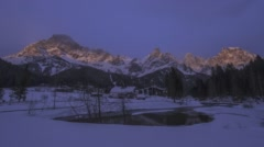 Day-to-night timelapse of wintry village at the foot of a snow-covered mountain. Stock Footage