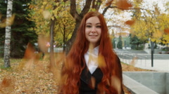 A girl with flowing red hair is standing under falling leaves in the park. Stock Footage