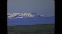 1971: a beautiful view of a coastal city or town with buildings on the water Stock Footage