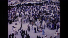 1971: crowd gathers in open marketplace in front of rows of tents  Stock Footage