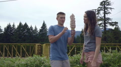 Cute Couple On Road Trip Stop For Huge Ice Cream Cone, Share It, Train Passes By Stock Footage