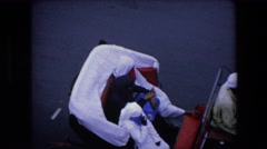 1971: three women in burkas riding in a horse-drawn coach down a paved street Stock Footage