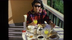 1971: an adult woman taking a hearty breakfast sitting on a terrace ALGERIA Stock Footage