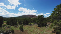 Camera Rising To Reveal Distant Red Mountain Cinder Cone Stock Footage
