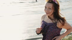 Happy young girl with flower in hair run on beach smile in camera. Sunny day Stock Footage