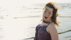 Happy young girl with flower in hair fastly run on beach smile in camera. Sunny Stock Footage