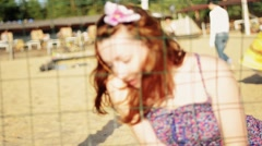 Pretty young girl with flower in hair fencing on beach look in camera. Summer Stock Footage