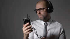 Businessman in a shirt and big headphones, listening to trendy track from your Stock Footage