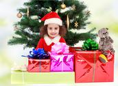 Little girl near the Christmas tree surrounded by gifts Stock Photos