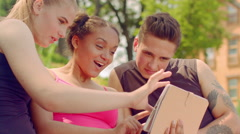 Young people watching photo on tablet outdoor. Young friends having fun Stock Footage