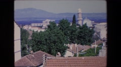 1971: a scenic view of a historical type town on a sunny day with mountains  Stock Footage