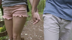 Closeup Of Couple Holding Hands, Hiking In The Woods, Woman Carries Wild Flowers Stock Footage