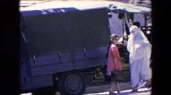 1971: a woman in a burka walking past military vehicles  Stock Footage