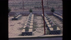 1971: view of a cemetery with rows of tombstones in a fenced area in the desert Stock Footage