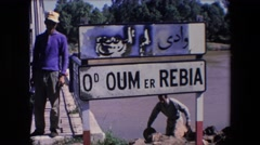 1971: a man is climbing stairs near a sign carrying a hat and a bag  Stock Footage