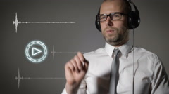 Businessman in a shirt and big headphones, click on the play button and start Stock Footage