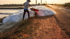 Peasant Unload Salt from Wheelbarrow to Heap by Lakes Stock Footage
