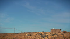 Wide shot of rural ,stone house in desert landscape Stock Footage