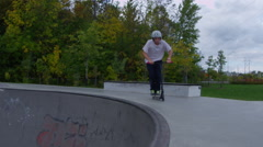 Ramped slow motion scooter in bowl with flip Stock Footage