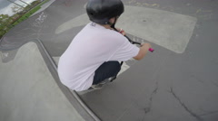 Scooter 360 spin over a jump in a skatepark Stock Footage