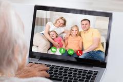 Close-up Of Grandmother Video Conferencing With Her Family On Laptop At Home Stock Photos