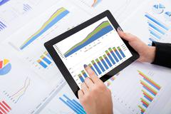 Close-up Of Businesswoman Analyzing Financial Graphs Using Digital Tablet On  Stock Photos