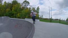 Scooter flip drop in on skatepark bowl Stock Footage