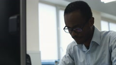 Young office worker wearing glasses using his laptop in the office Stock Footage