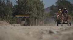 Donkey cart travelling along dusty road Stock Footage