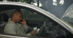 4K Man on cell phone in broken down car while lady recovery worker checks engine Stock Footage