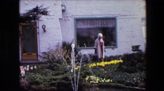 1967: a woman outdoor with gardening gloves admiring her flowers AMSTERDAM Stock Footage