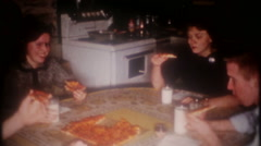 Teenagers around the kitchen table eating pizza, 3701 vintage film home movie Stock Footage
