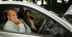 4K Couple stranded in broken down car henpecked man gets nagged by girlfriend Stock Footage