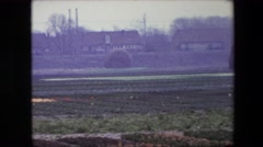 1967: row of buildings adjacent crop fields in bloom BRUSSELS, BELGIUM Stock Footage