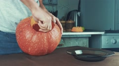 Male hands scooping out seeds and contents of pumpkin. Halloween theme, jack Stock Footage