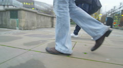 4K Low angle view of 2 pairs of legs walking through the city Stock Footage
