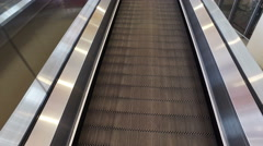 Long walkway of escalator at international airport terminal, moving POV Stock Footage