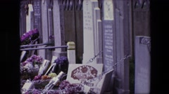 1967: a view of a cemetery with various tombstones chained to a wall  Stock Footage