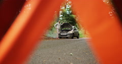 4K Stressed man looking under hood of broken down car on country road Stock Footage