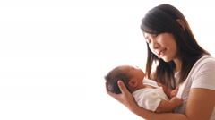 Asian young pretty mother kissing her little baby with love Stock Footage