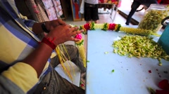 Undentified indian man brides beautiful colourful flower garland at KL market Stock Footage