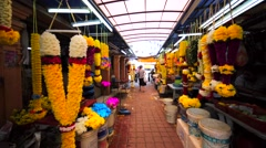 Walking between market stands with colourful flower garland at KL street market Stock Footage