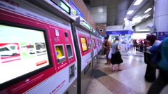 Tourists buy tickes for KL Rapid train using ticket machines. Malaysia Stock Footage