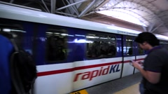 Arriving Kuala Lumpur Rapid train and waiting tourists. Malaysia Stock Footage