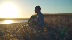 Handsome man sitting with old dog in field at sunset Stock Footage